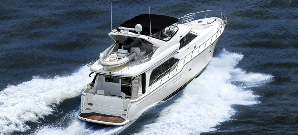 Yacht with fly deck and dinghy cruising away with waves of water breaking along side it